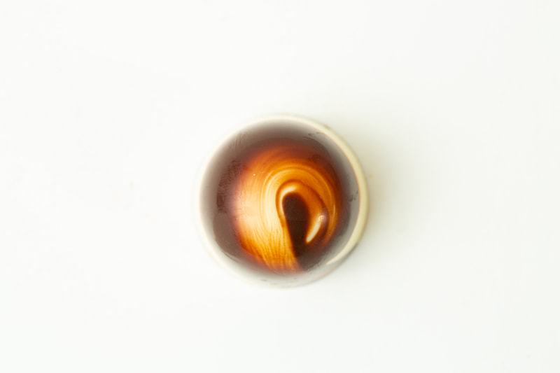 White and dark marbled shell filled with a creamy milk and hazelnut ganache.